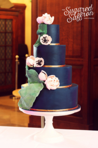 Navy wedding cake with pink flowers and banana leaves by Sugared Saffron