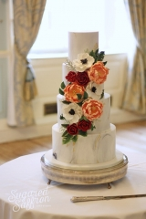 Anemones and peonies on grey wedding cake at dartmouth house