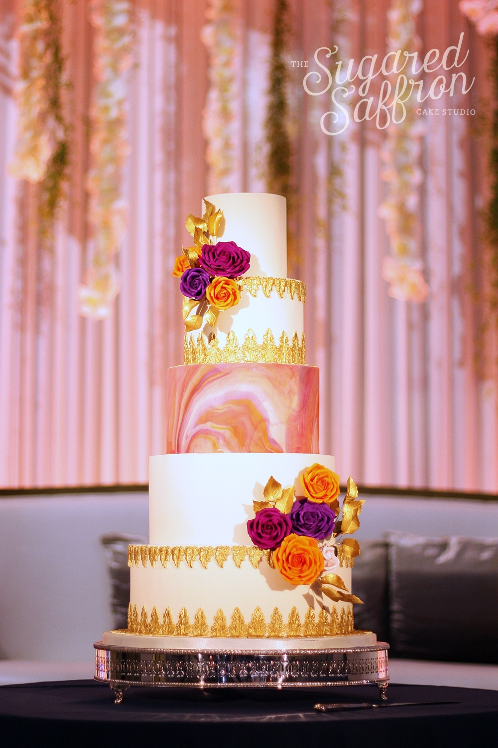 arabian sunset cake with marbled orange sugarpaste and purple and orange roses