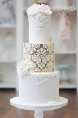 white baroque wedding cake with gold leaf and damask