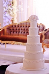 white cake with baroque scrolls and sugar roses