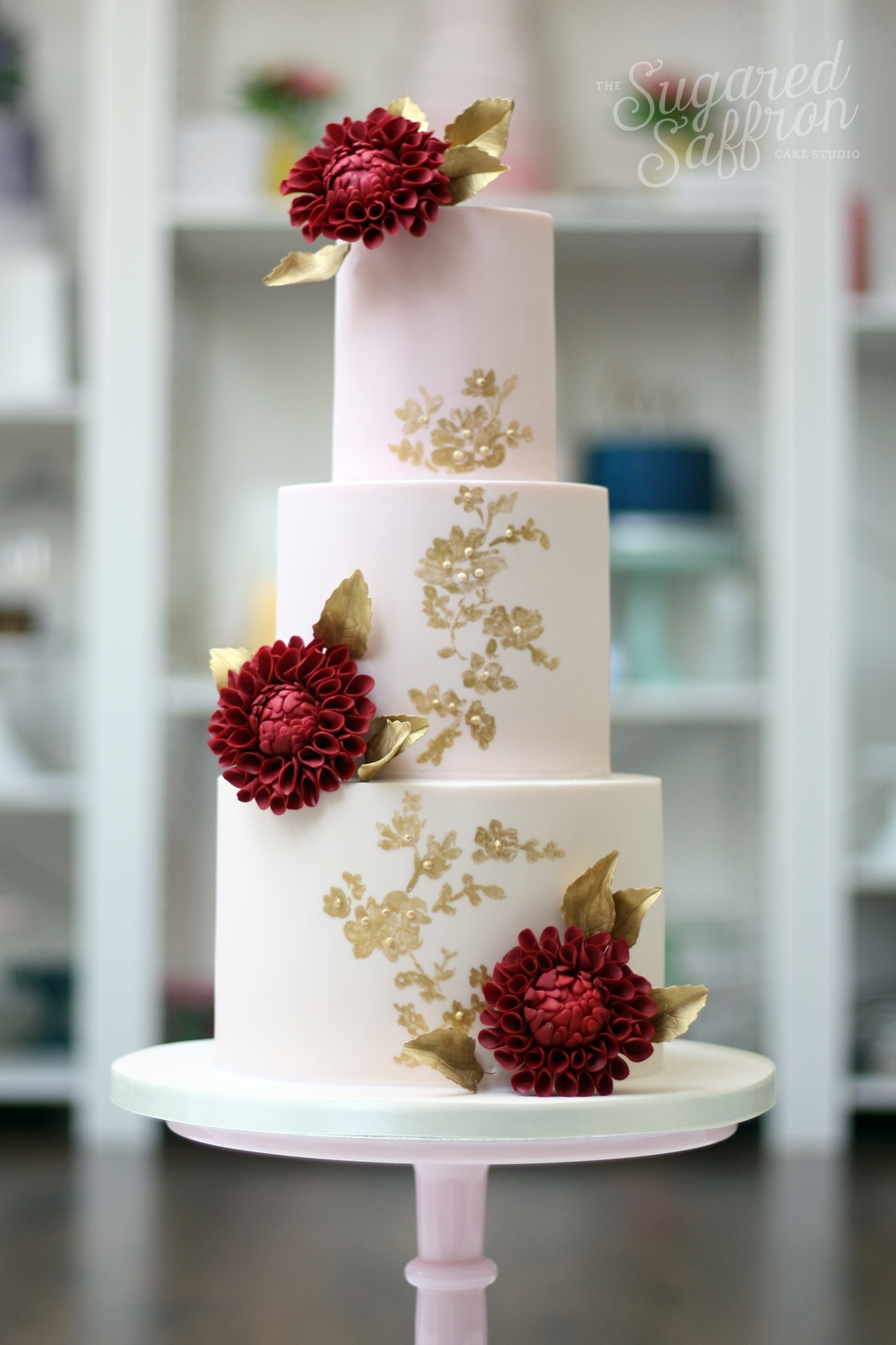 pink cake with gold painting and red dahlias