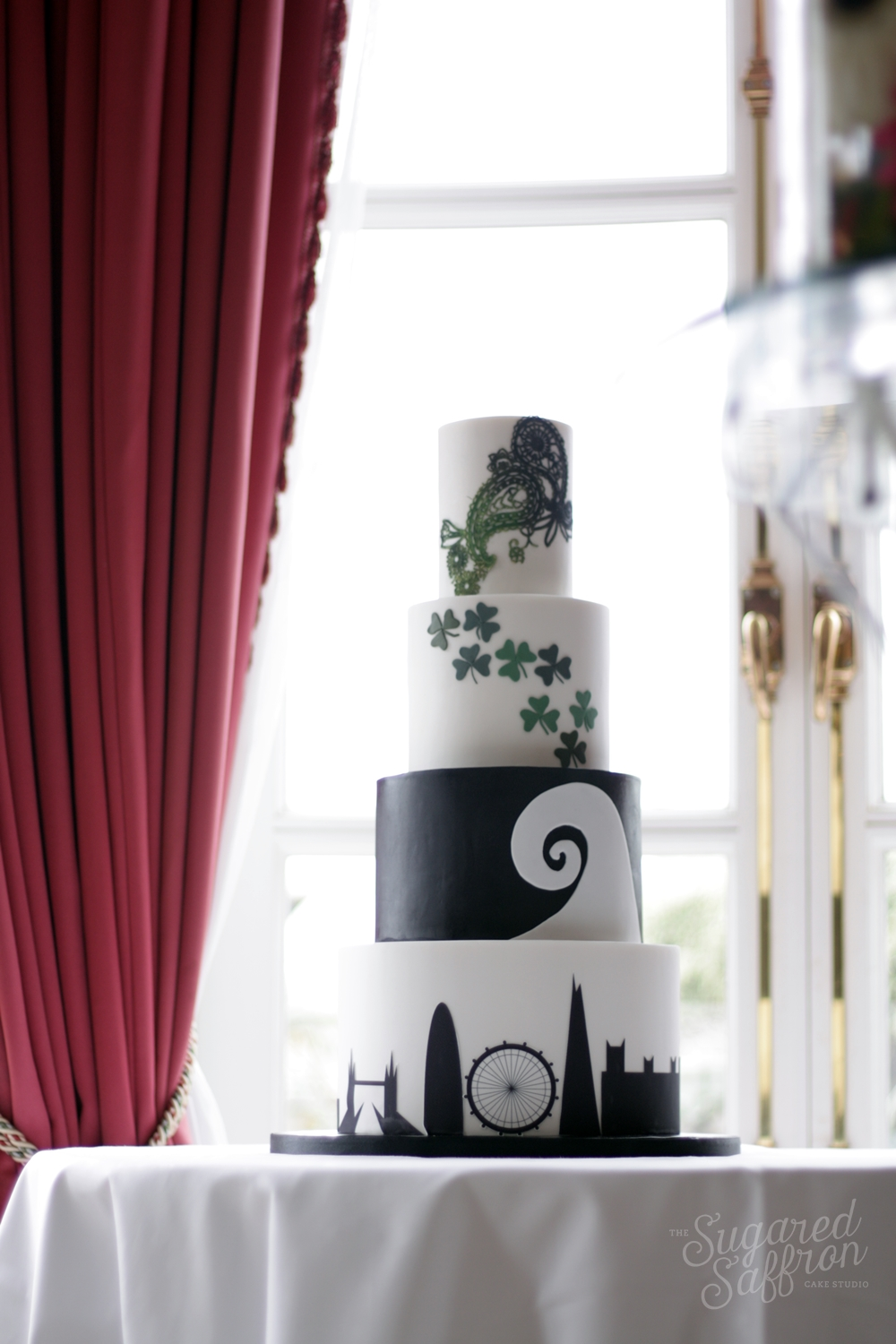 black and white wedding cake with london silhouette maori koru and shamrock
