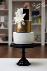 Black and gold leaf wedding cake with marble and folded fabric design