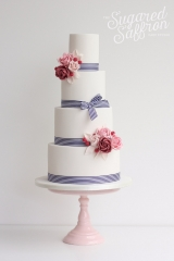 white cake with blue striped ribbon and pink sugar flowers