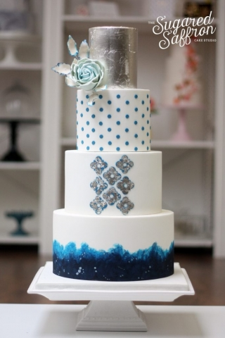white cake with blue and silver leaf decoration