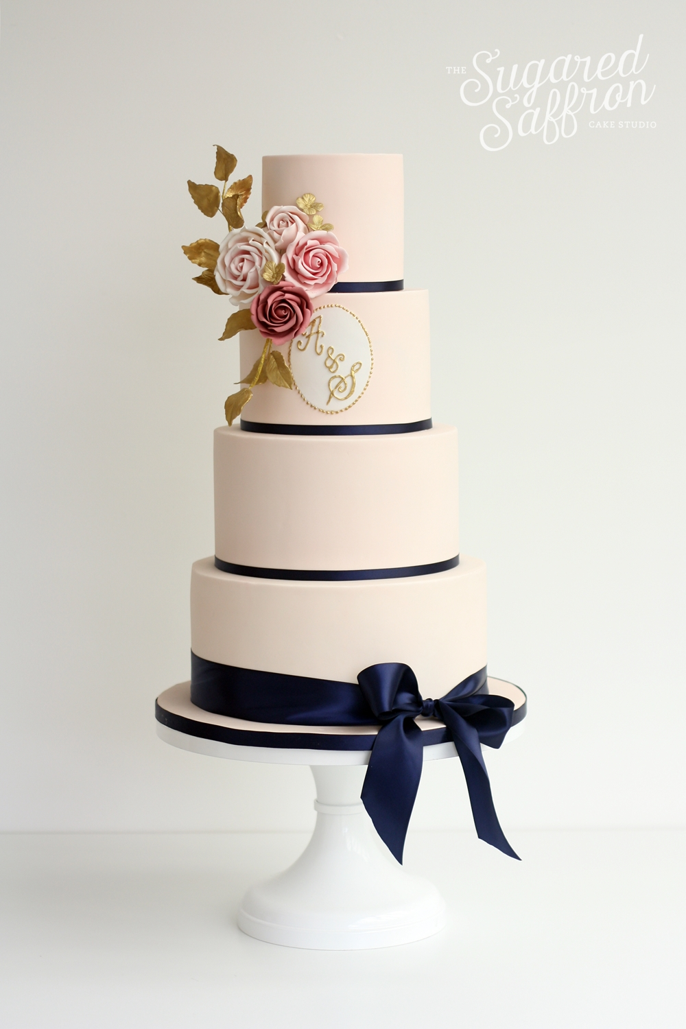 blush wedding cake with navy ribbon and pink sugar roses