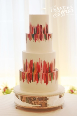 shades of red brushstrokes painted on white wedding cake at claridges hotel london