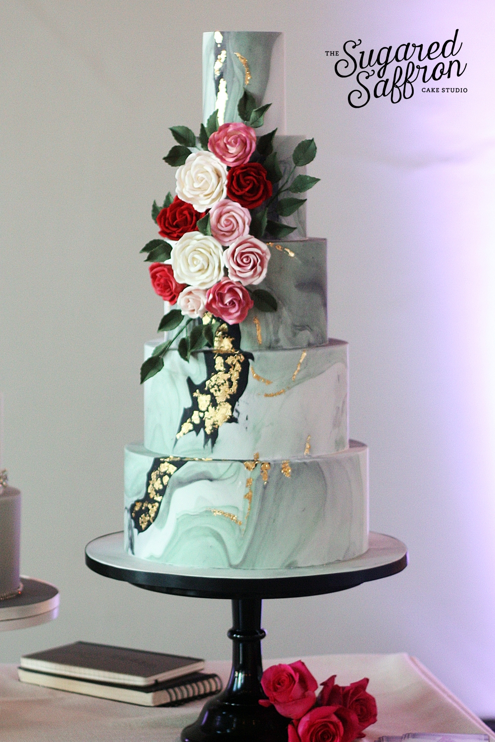 dark marble wedding cake with red white pink and white roses and gold leaf