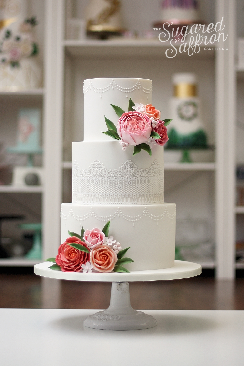 david austin and roses in coral and pink on white wedding cake