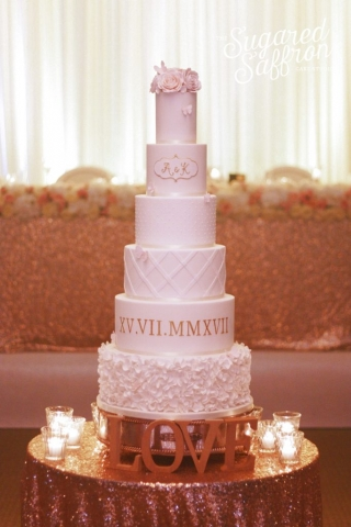 white wedding cake with gold roman numerals
