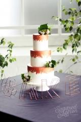 white wedding cake with copper brushstrokes and fresh foliage