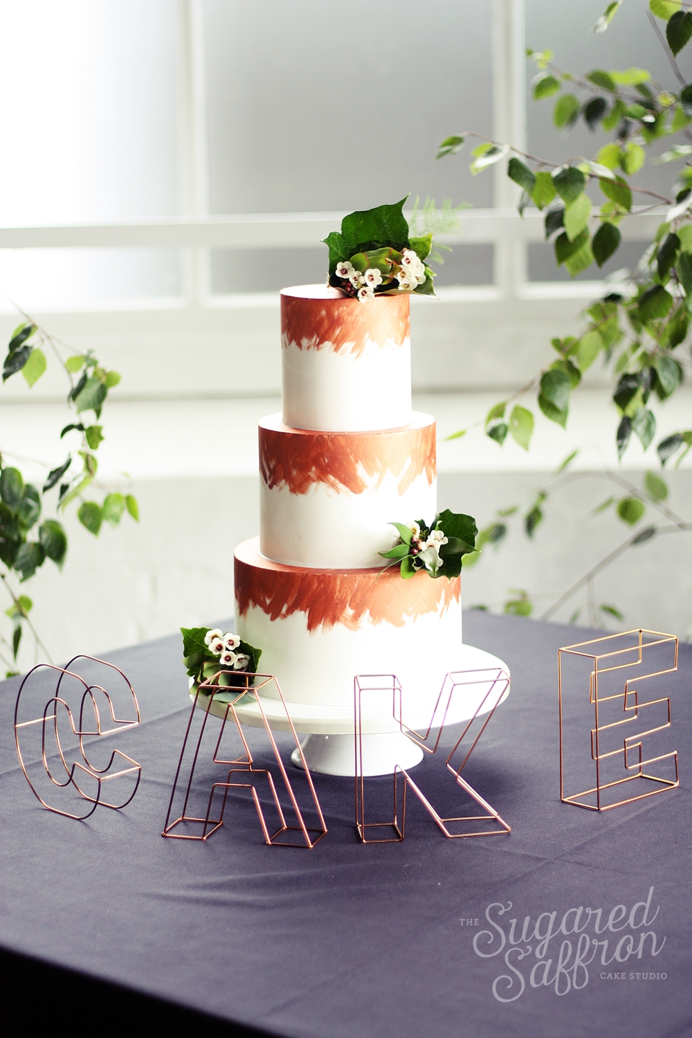 white wedding cake with copper brushstrokes and fresh foliage