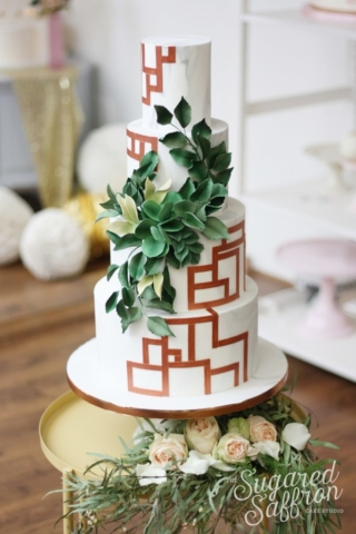 Copper geometric line patterns with sugar foliage on marble