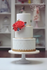 white cake with pillow texture and large coral roses and david austin