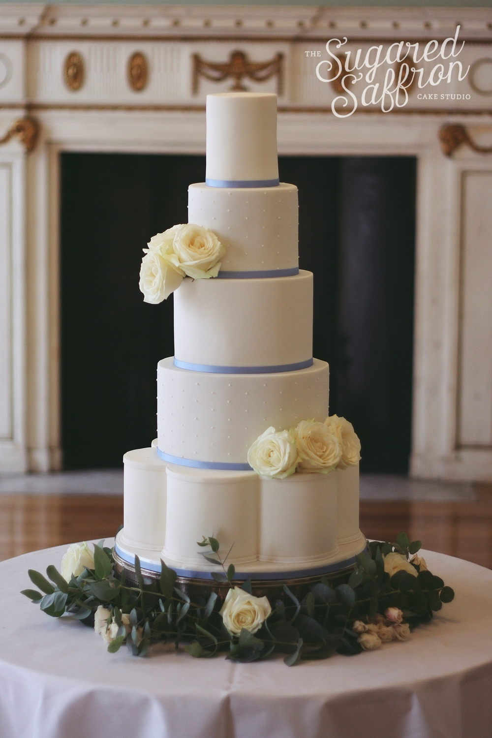 white cake with cornflower blue ribbon and fresh roses