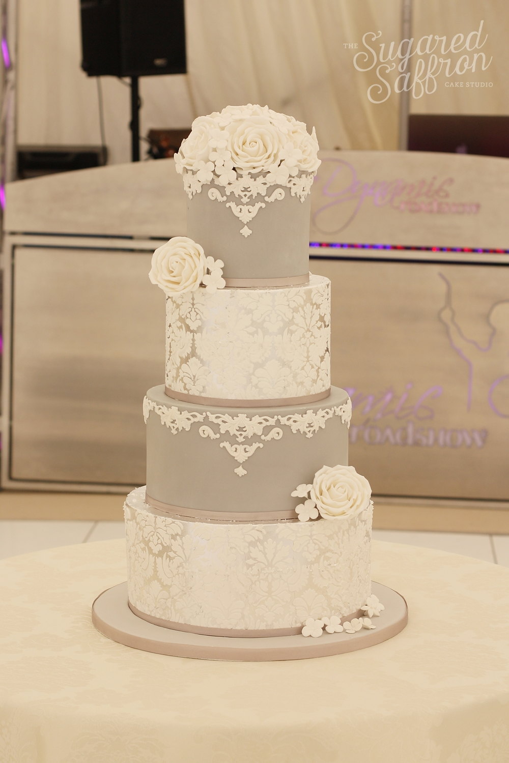grey cake with silver leaf and white damask. white sugar roses