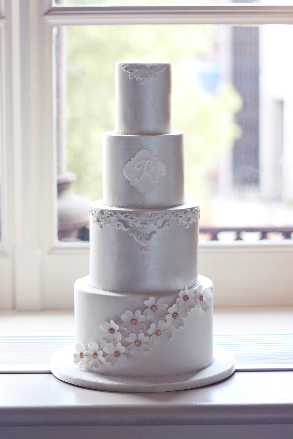 silver cake with monogram and sugar dogwood flowers