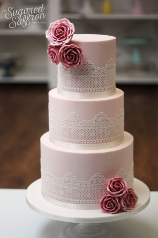 Pink wedding cake with white lace and dusky pink roses