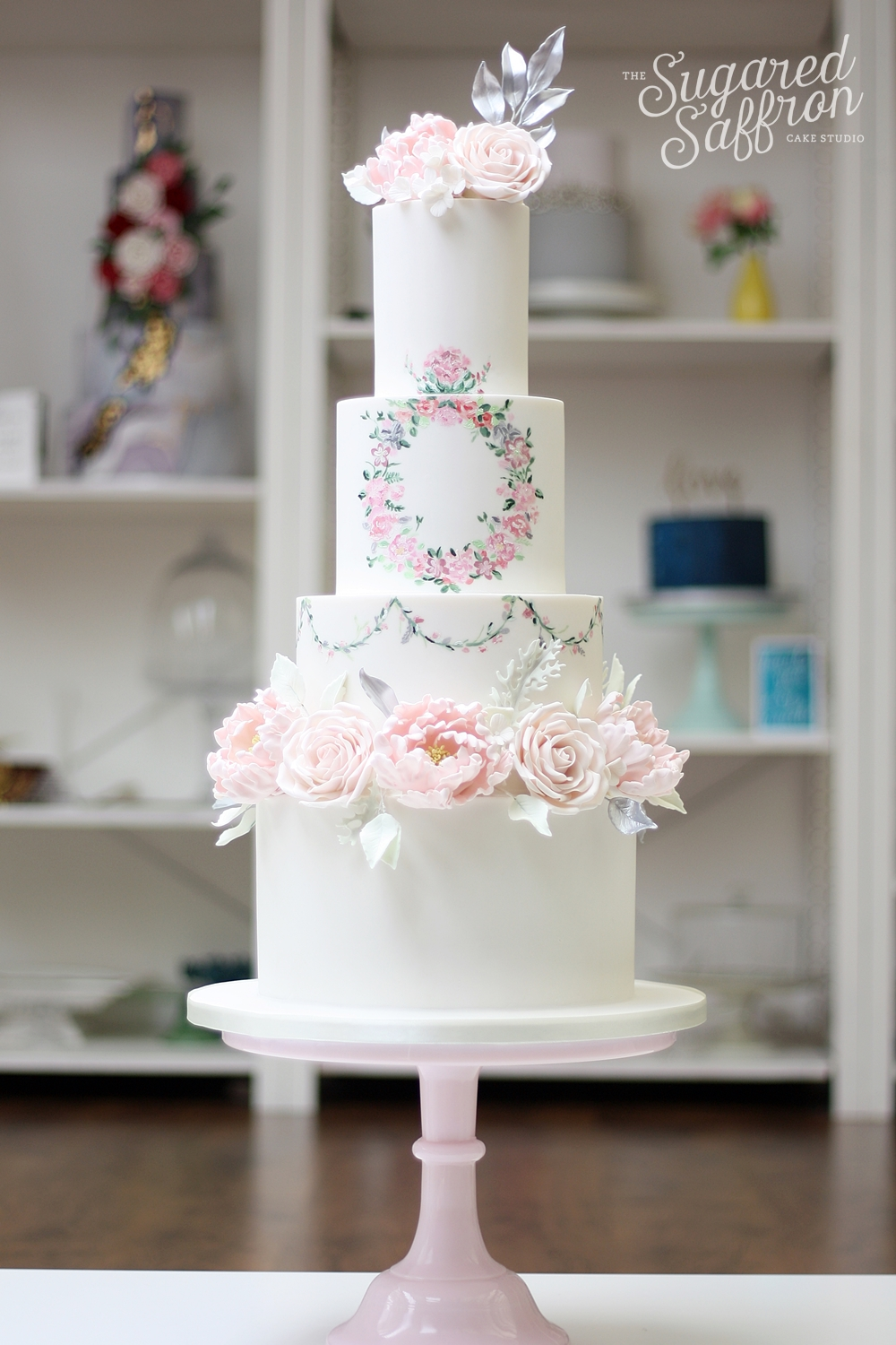 painted flowers in watercolour style on white wedding cake with pink english roses