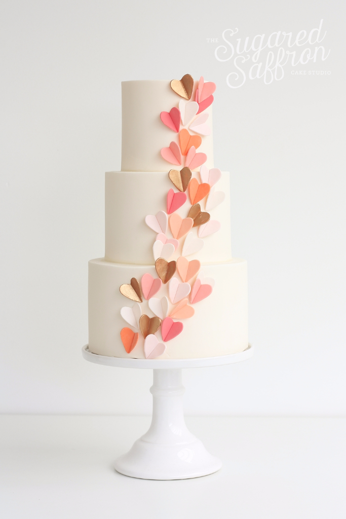 small folded sugar hearts in orange and pink on ivory wedding cake