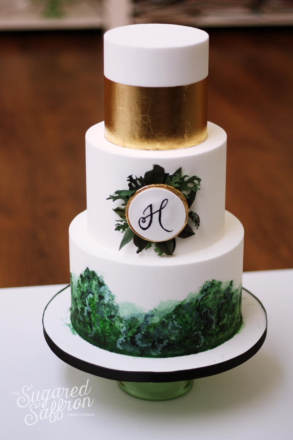 green watercolour wedding cake with gold leaf and monogram