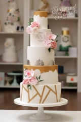 rusted gold and white wedding cake with geometric lines and pink sugar flowers