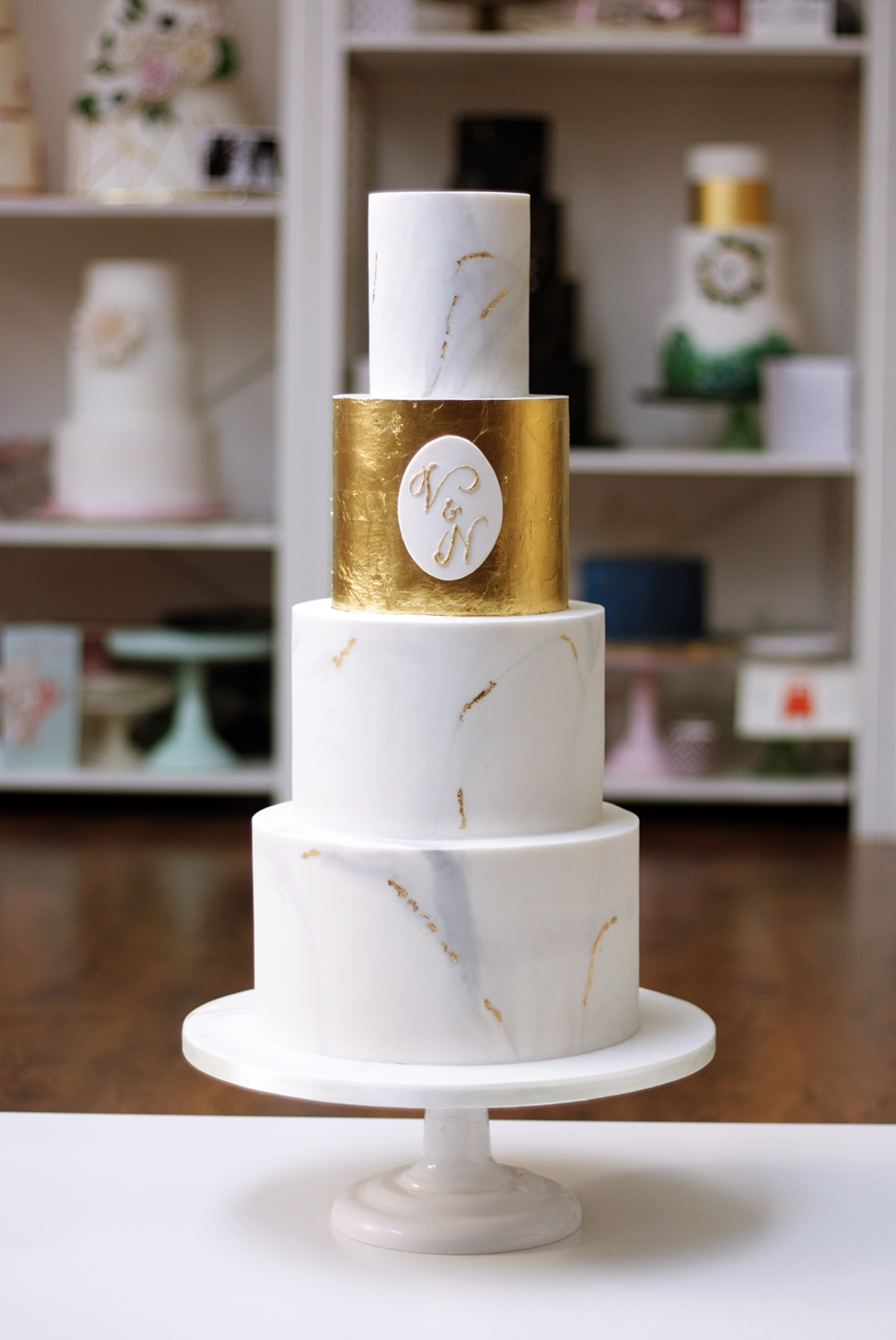 gold leaf tier with monogram on marbled grey wedding cake