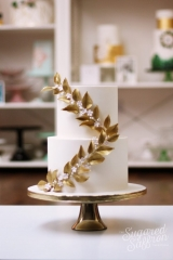 ivory wedding cake with climbing gold leaves and pink blossoms