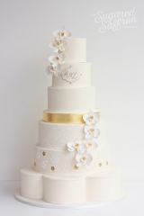 large ivory wedding cake with white orchids and gold leaf