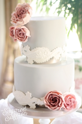 Grey wedding cake with white lace detail and dark pink roses