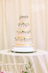 handpainted pink wedding cake with gold ribbon