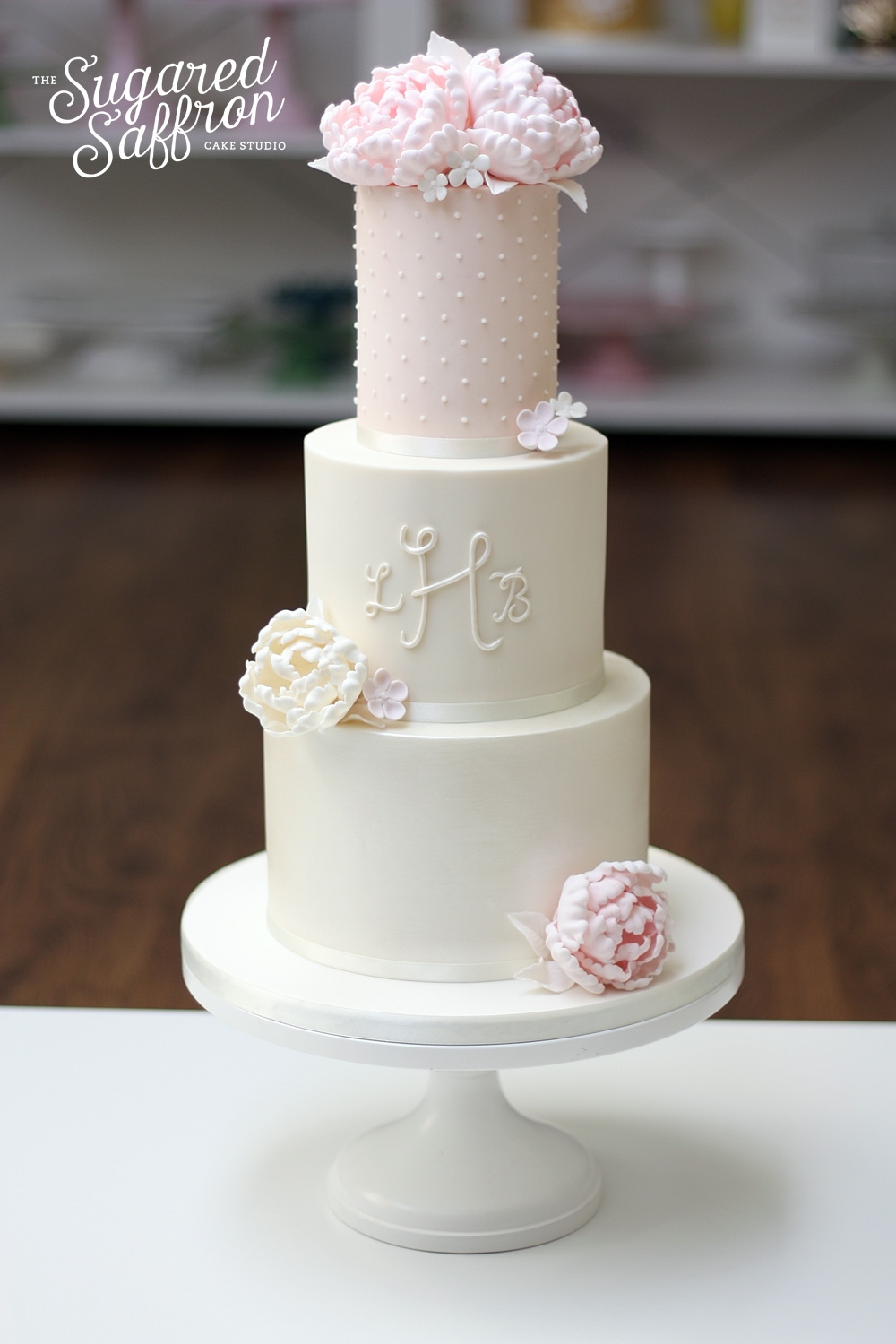 Ivory and blush wedding cake with monogram and peonies