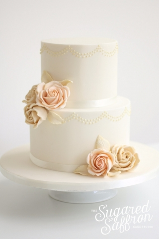 ivory cake with piped swags and sugar roses in ivory and peach