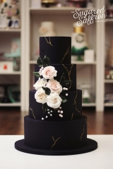 Black cake with gold kintsugi lines and sugar flowers