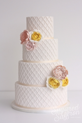 White wedding cake with lattice and sugar flowers in pink and yellow