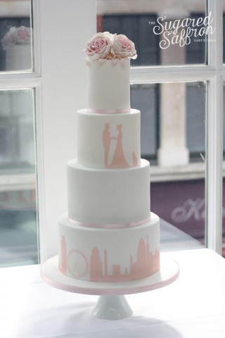pink silhouette of london skyline and couple on white cake