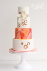 orange and pink marble wedding cake with hexagons and magnolia sugar flowers in white
