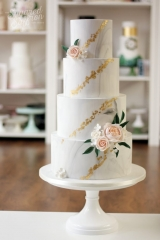 light marble wedding cake with peach roses and gold