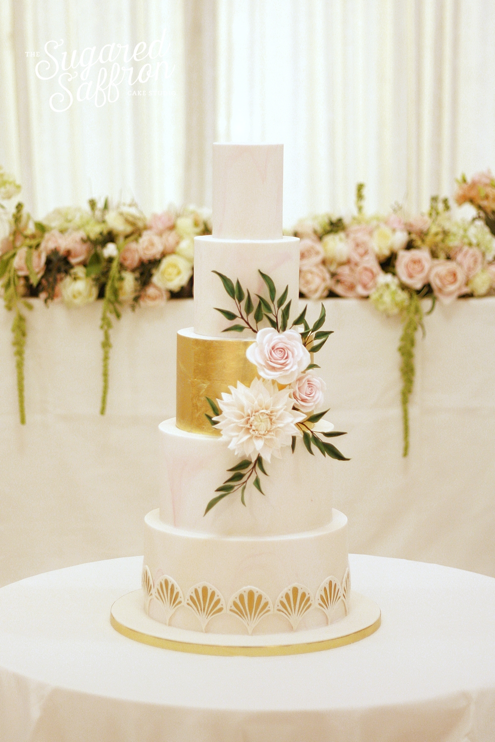 Pale pink marble cake with art deco fans. With cafe au lait dahlia and roses