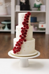 mini red rose cascade on ivory cake with gold leaf marks