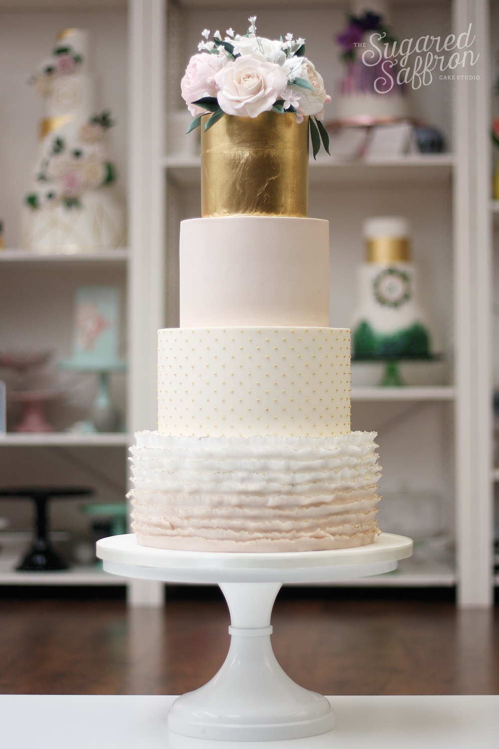bouquet of sugar flowers on gold leaf and mink coloured tiers. Ruffles on bottom tier.