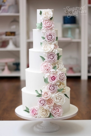 pink lilac peach and white sugar roses cascading from white cake with green leaves