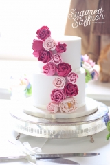 dark and light pink cascade of sugar flowers on a white cake