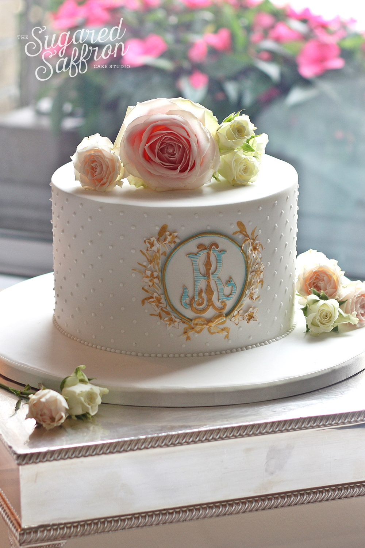 single tier wedding cake with regal monogram and fresh flowers