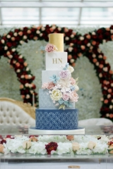 navy and light blue cake with sugar flowers in neutral pastel tones