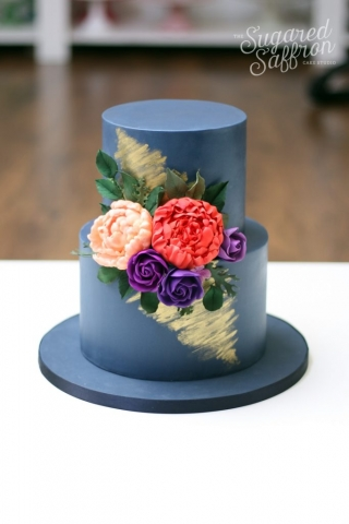 navy wedding cake with gold brushes. Coral and purple flowers