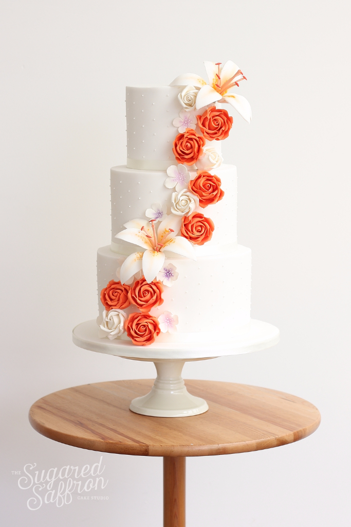 orange and white roses and lilies on white wedding cake