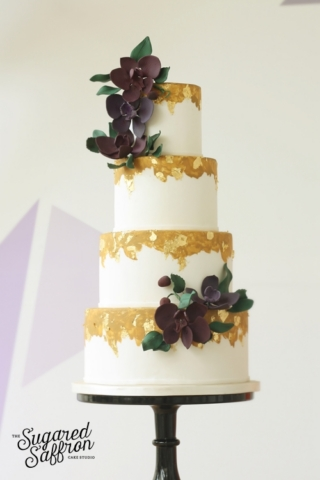 dirty gold and white wedding cake with purple orchids