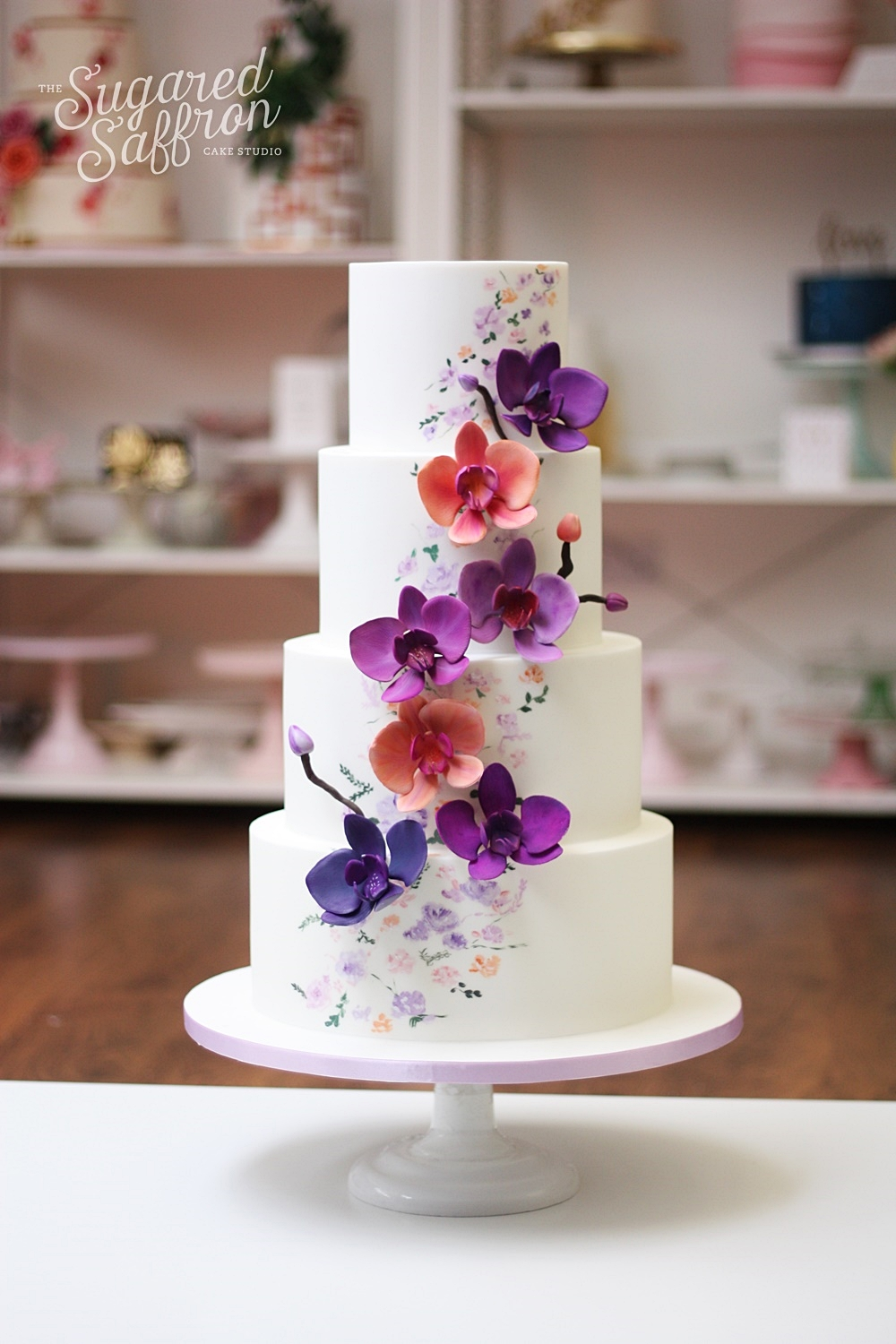 painted flowers on white cake with roses in purple and orange